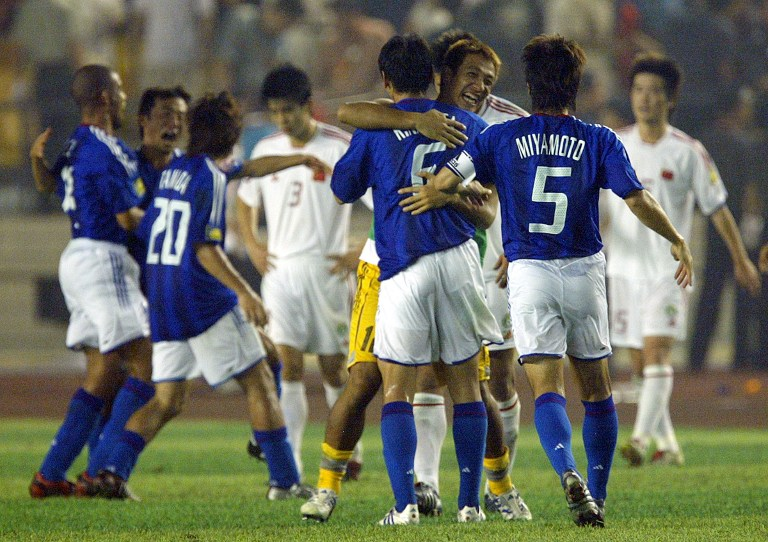 Japan's captain Miyamoto Tsuneyasu (#5) joins his teamates to celebrate their win in the final of the Asia Cup 2004 in the Workers Stadium in Beijing 07 August 2004. Holders Japan beat China 3-1 to take the Cup back to Japan.   AFP PHOTO/Peter PARKS